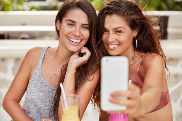 Bruna adorabili femmine soddisfatte con sorrisi brillanti si divertono insieme, posano per selfie nella fotocamera del moderno smart phone