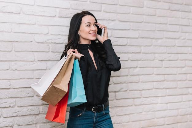 Bruna alla moda con borse in chat via telefono
