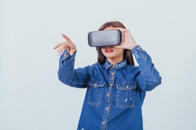 Bruna bella donna in posa, indossando jeans indossare, utilizzando le cuffie da realtà virtuale occhiali vr