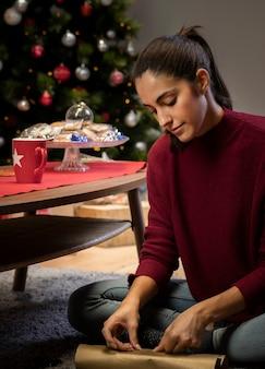 Bruna che sta confezionando un regalo