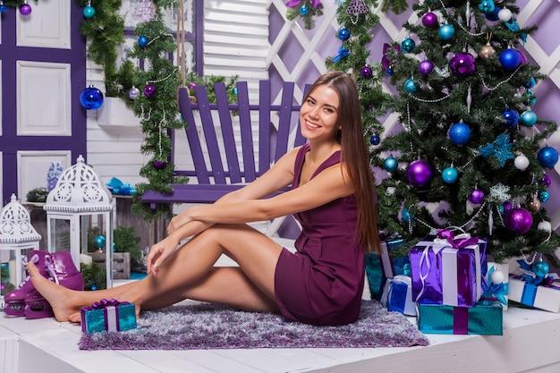 Bruna con le gambe lunghe in un vestito turchese che si siede sull'oscillazione viola sopra