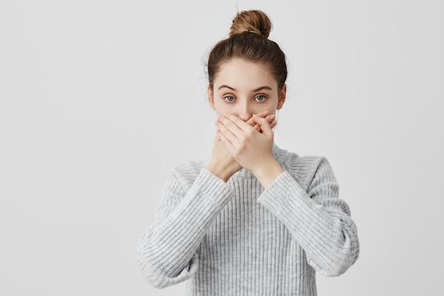 Bruna femmina di 30 anni che copre la bocca con entrambe le mani mantenendo il silenzio. fedele amica che promette di non dire segreti in maniera fidata. persone, concetto di atteggiamento