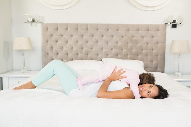 Bruna gioca con il suo bambino sul letto