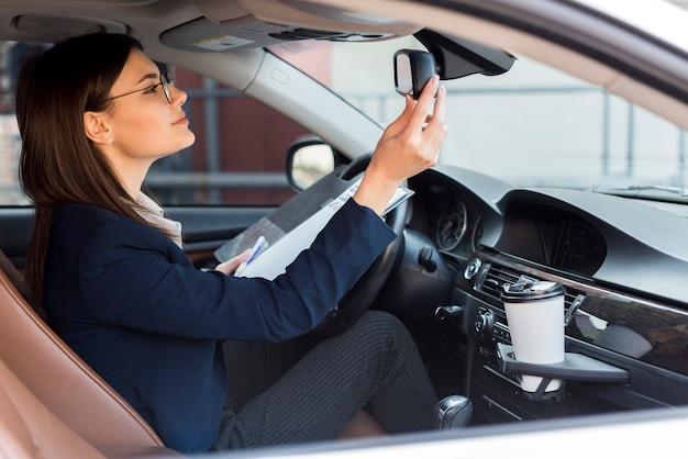 Bruna imprenditrice all'interno di un'auto