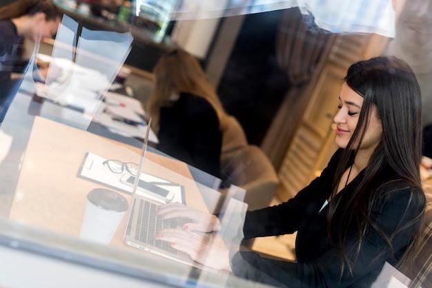 Bruna imprenditrice attraverso una finestra con il portatile