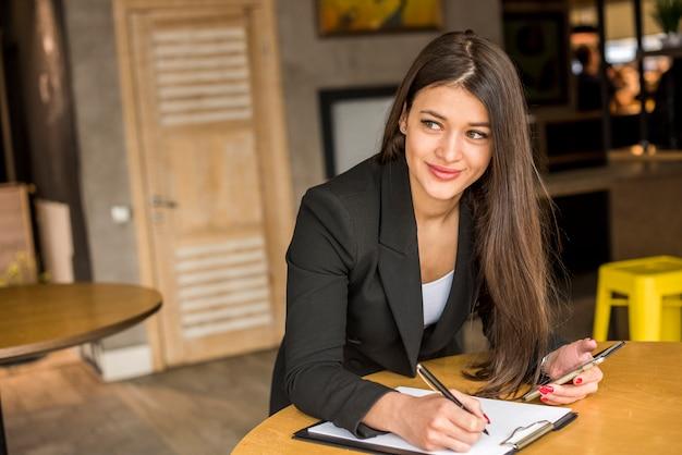 Bruna imprenditrice scrivendo su un documento