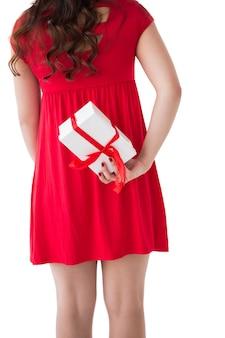 Bruna in abito rosso nascondendo il regalo