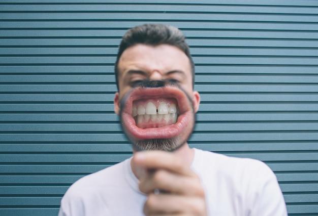 Bruna in camicia bianca è in piedi al muro e in posa. tiene in mano il loup e mostra i denti sulla telecamera. il ragazzo ha i denti grandi. isolato su strisce