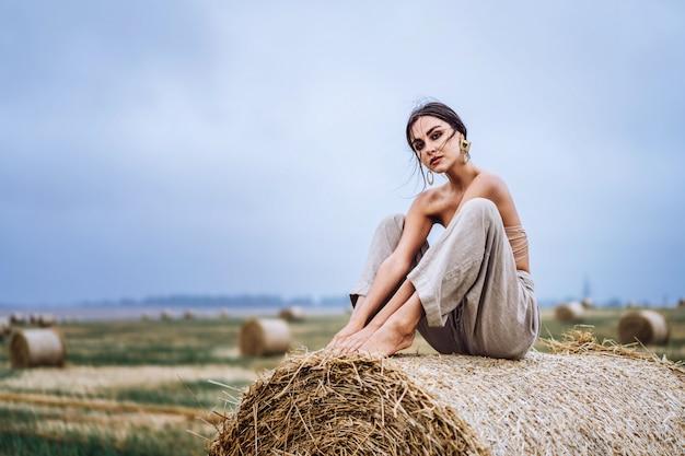 Bruna in pantaloni di lino e spalle nude seduto su balle di fieno in una calda giornata d'autunno. donna che guarda l'obbiettivo. dietro di lei c'è un campo di grano