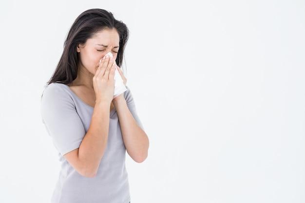 Bruna malata che soffia il naso