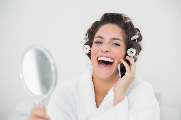 Bruna naturale che ride usando il telefono