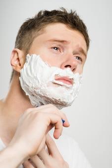 Bruna ragazzo con i capelli corti scuri radersi la faccia con il rasoio