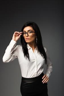 Bruna sexy con gli occhiali, in una camicetta bianca con una gonna di pelle nera.