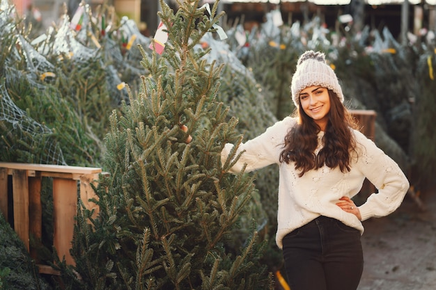 Brunetta carina in un maglione bianco con albero di natale