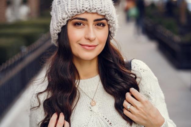 Brunetta carina in un maglione bianco in una città