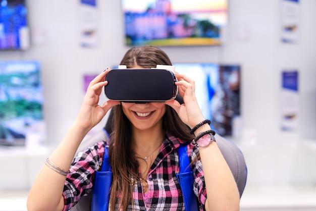 Brunette caucasico sorridente emozionante con capelli lunghi che provano realtà virtuale