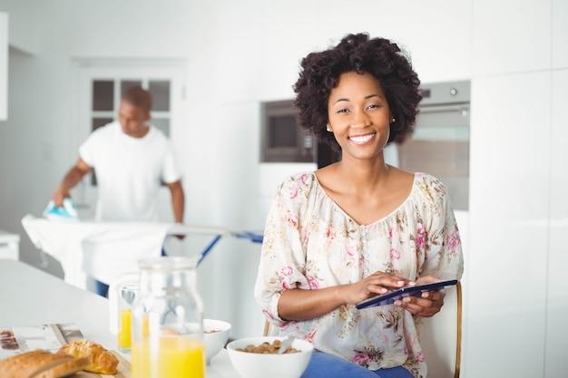 Brunette che utilizza compressa nella cucina e la stiratura del suo ragazzo