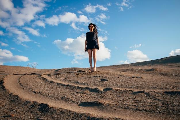 Brunette della donna del ritratto di stile di vita che rimbalza in sabbia