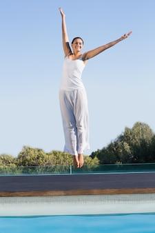 Brunette felice che salta a bordo piscina con le braccia alzate