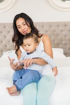 Brunette felice che tiene il suo bambino e che utilizza smartphone nella camera da letto
