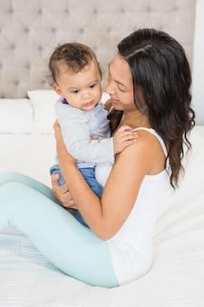 Brunette felice che tiene il suo bambino sul letto