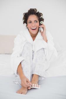Brunette naturale di risata che applica lo smalto e che effettua una chiamata