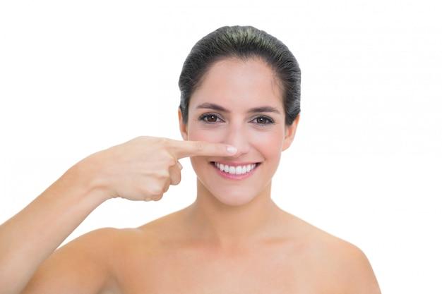 Brunette nudo sorridente che tocca il suo naso