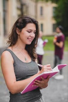 Brunette ragazza in piedi in piedi notebook di scrittura