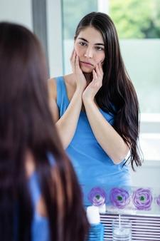 Brunette triste in bagno guardando lo specchio