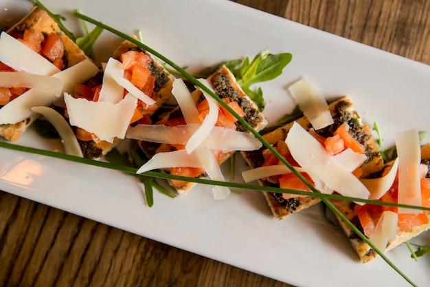 Bruschetta al pesto di olive e aglio, con pomodorini e foglie di parmigiano