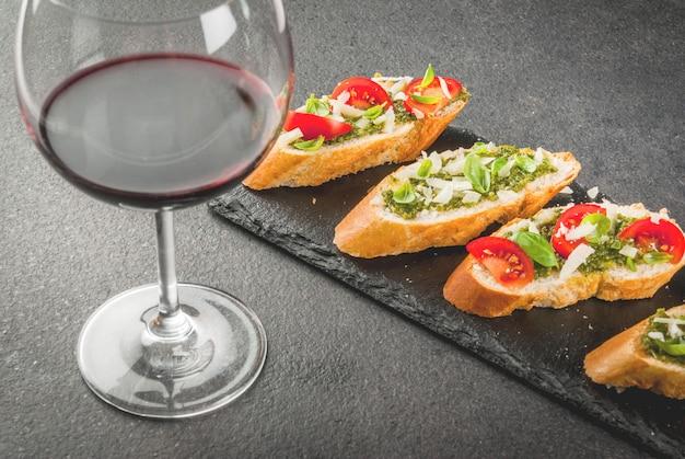 Bruschetta al pesto, parmigiano, pomodori e basilico sul vassoio con vino