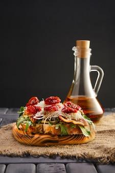 Bruschetta con formaggio, pancetta fritta, olive tritate e pomodori secchi