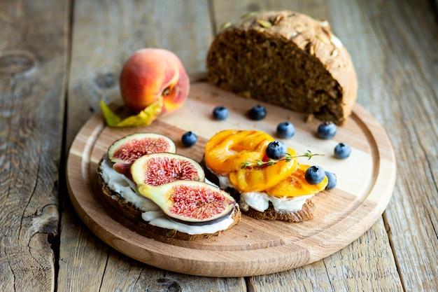 Bruschetta con frutti di bosco, fichi e pesca su formaggio. pane