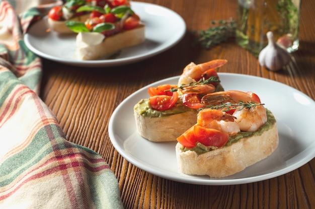 Bruschetta con gamberi, salsa al pesto di basilico e mozzarella su un piatto bianco su un fondo di legno.