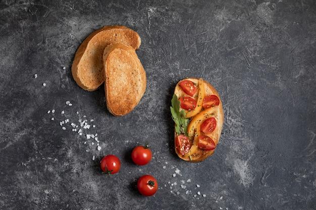 Bruschetta con i pomodori nelle mani su un fondo scuro, vista superiore.