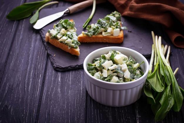Bruschetta con insalata di aglio orsino su sfondo di ardesia