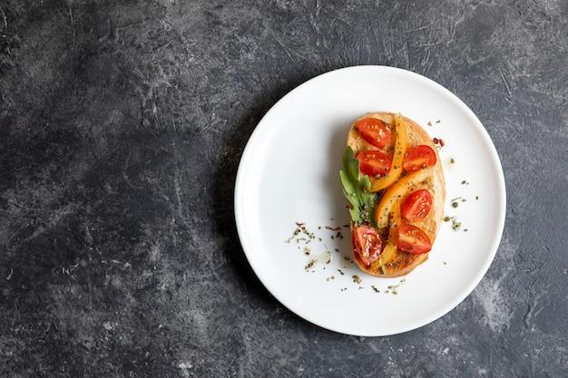 Bruschetta con pomodori su un piatto bianco su sfondo scuro. vista dall'alto, copia spase