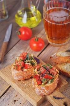 Bruschetta con pomodori tritati, basilico ed erbe su pane croccante grigliato.