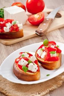 Bruschetta con pomodoro, feta e basilico