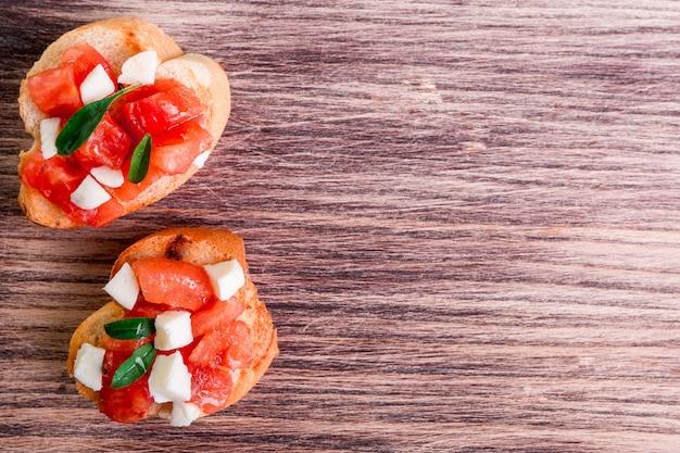 Bruschetta con pomodoro, mozzarella e basilico su fondo di legno. vista dall'alto. copia spazio.