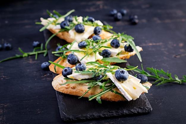 Bruschetta. crostini di pane tostato con bacche fresche di mirtillo e miele, brie, rucola. cucina italiana