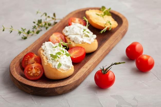 Bruschetta di pane tostato antipasto italiano con crema di formaggio e pomodori. pasto delizioso e sano, copia spazio