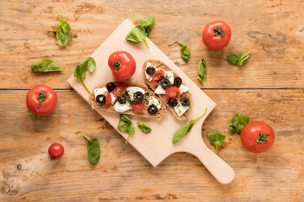 Bruschetta fresca sul tagliere di legno circondato con spinaci e pomodoro