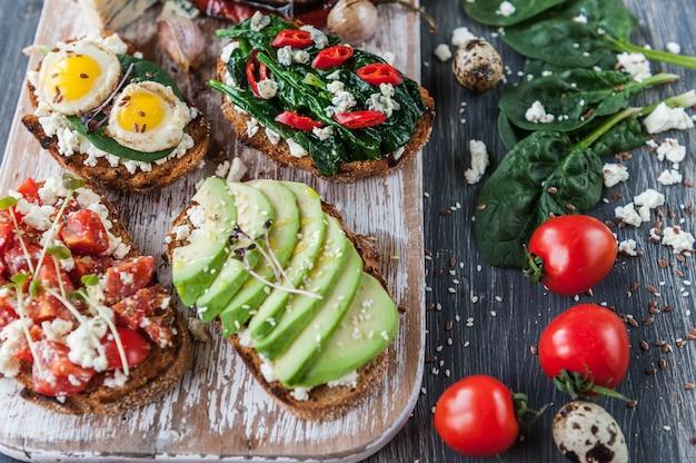 Bruschetta gustosa e deliziosa con pomodori, spinaci, peperoncino rosso di avocado feta e gorgonzola.