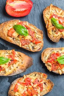Bruschetta italiana con pomodori arrostiti, mozzarella e