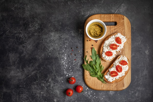 Bruschetta italiana con pomodori arrostiti, mozzarella ed erbe su un tagliere.