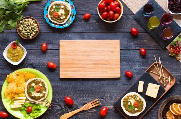 Bruschetta saporita e deliziosa con avocado, pomodori, formaggio, erbe, patatine e liquore su legno