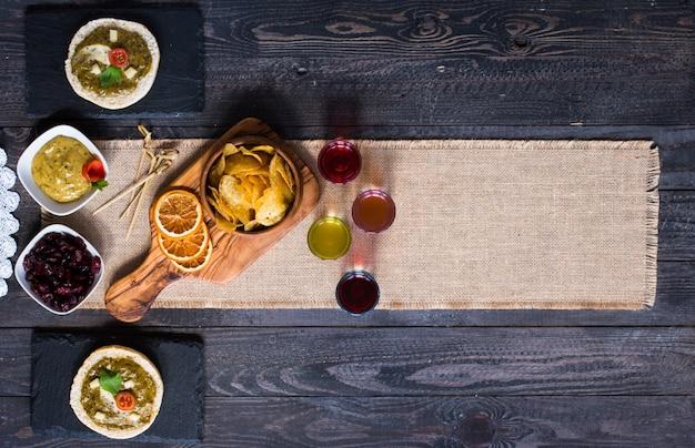 Bruschetta saporita e deliziosa con avocado, pomodori, formaggio, erbe, patatine e liquore, su un fondo di legno.
