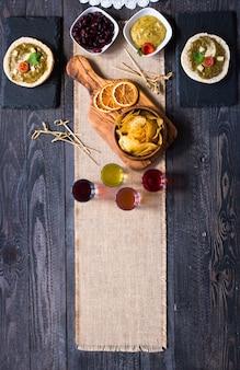 Bruschetta saporita e deliziosa con i chip e il liquore delle erbe del formaggio dei pomodori dell'avocado su un fondo di legno.