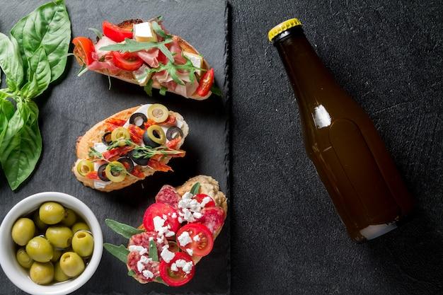 Bruschetta tradizionale. antipasti italiani con jamon, salsiccia guanchial, olive, ricotta, rucola e pomodori su sfondo nero